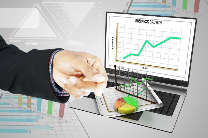 Hombre de negocios que muestra el ordenador portátil, concepto del crecimiento del negocio imagen de archivo