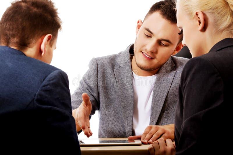 Hombre de negocios que muestra a la gente algo en la tableta imagenes de archivo