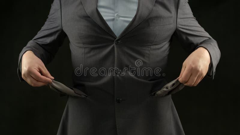 Hombre de negocios que muestra los bolsillos vacíos, la crisis y la inflación, concepto del desempleo foto de archivo