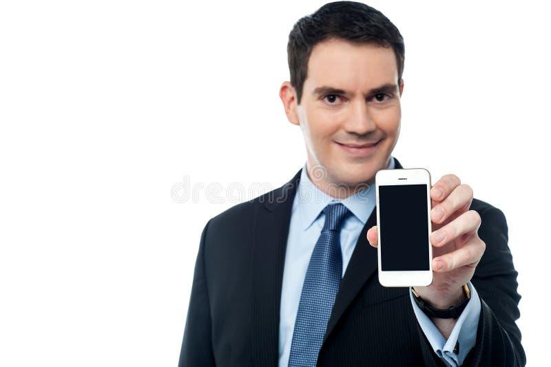 Hombre de negocios que muestra un teléfono móvil fotografía de archivo