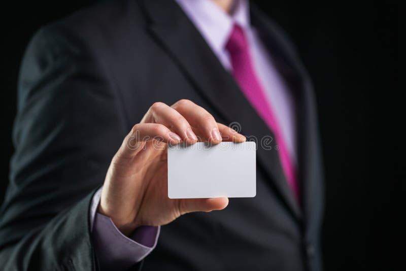 Hombre de negocios que muestra una tarjeta de visita en blanco aislada, ascendente cercano foto de archivo libre de regalías