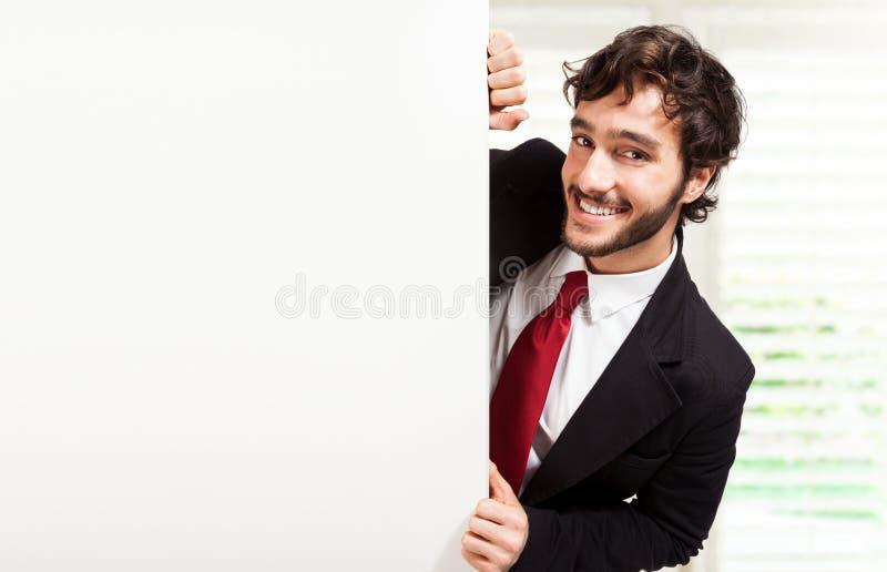 Hombre de negocios que muestra a una tarjeta en blanco fotografía de archivo