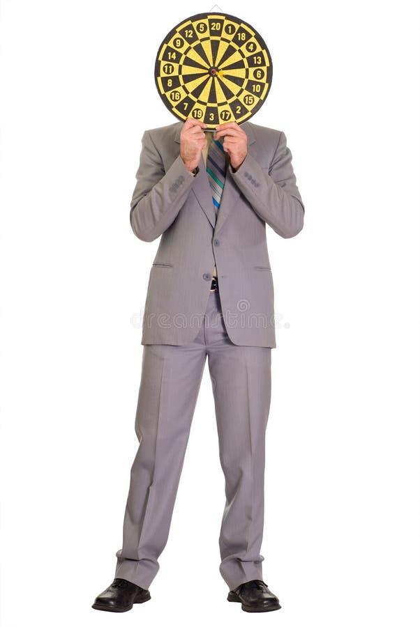 Hombre de negocios que oculta detrás de Dartboard imagen de archivo