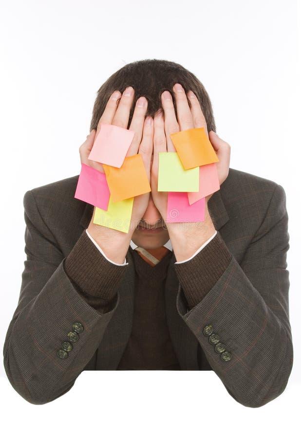 Hombre de negocios que oculta detrás de etiquetas engomadas fotografía de archivo libre de regalías