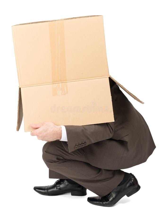 Hombre de negocios que oculta detrás de la caja foto de archivo