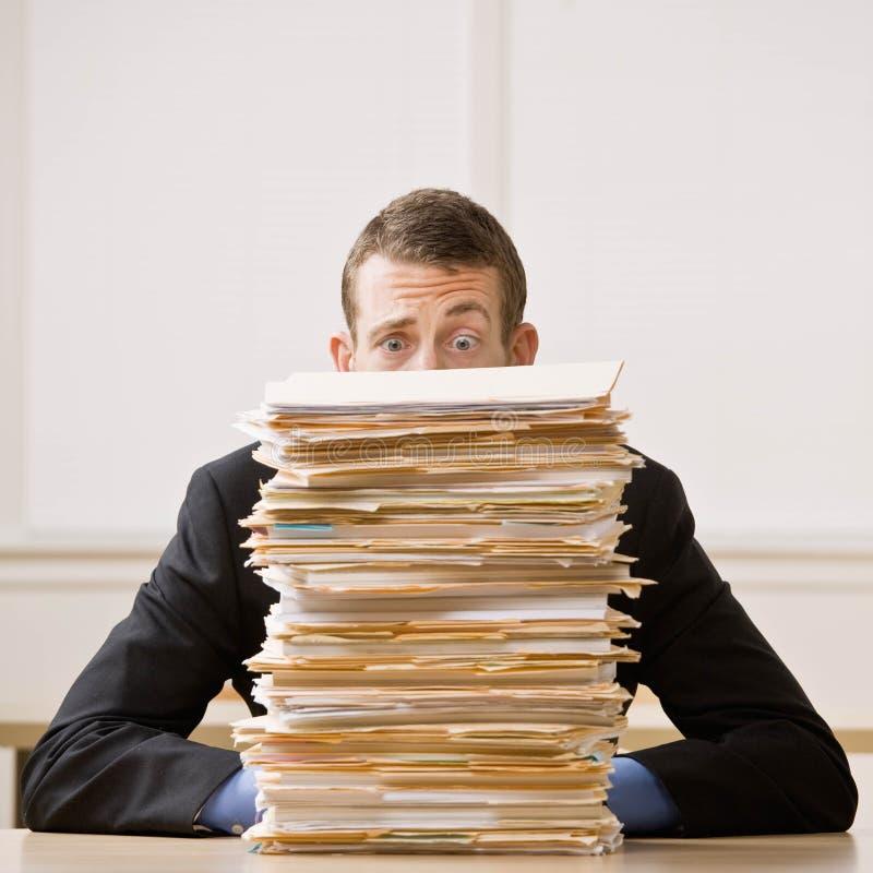 Hombre de negocios que oculta detrás de la pila alta de carpetas imagen de archivo libre de regalías