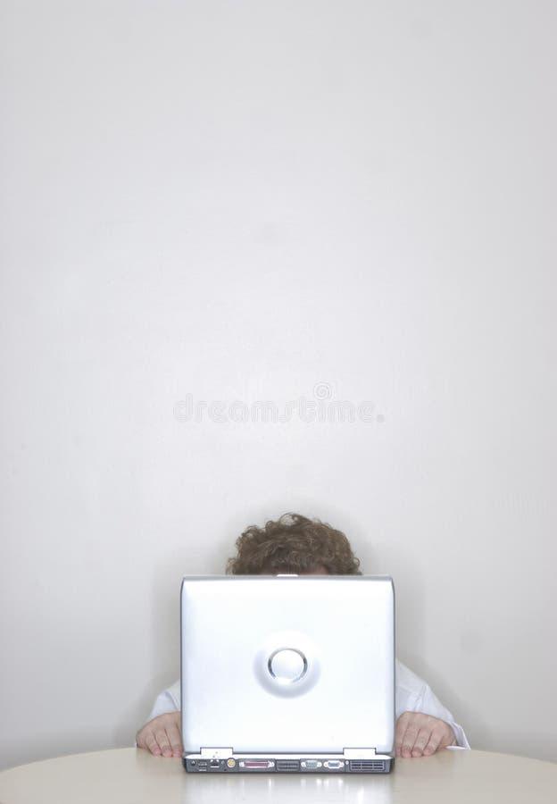 Hombre de negocios que oculta detrás de lapt foto de archivo