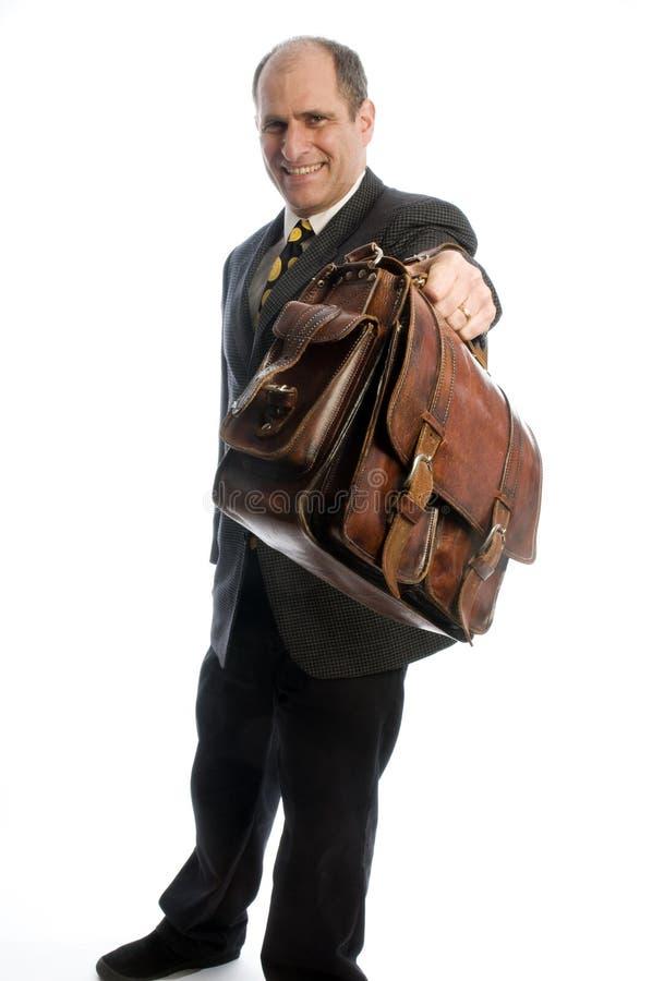 Hombre de negocios que ofrece el bolso de mano de cuero costoso foto de archivo libre de regalías