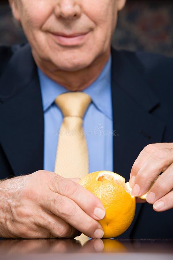 Hombre de negocios que pela una naranja imagen de archivo libre de regalías