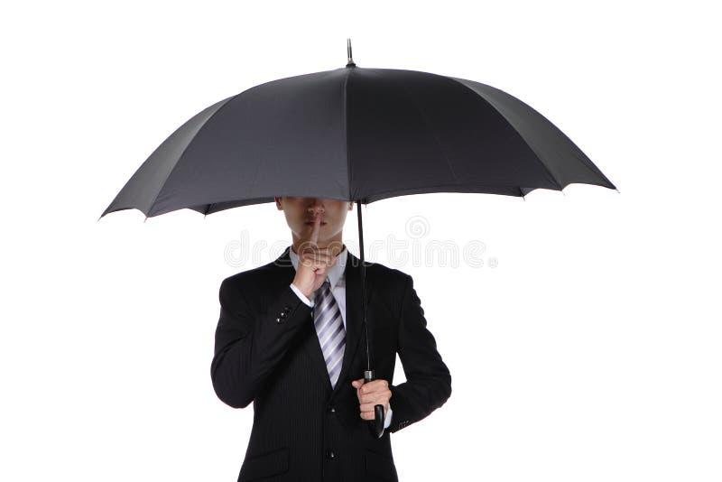 Hombre de negocios que pide silencio con el paraguas imagen de archivo