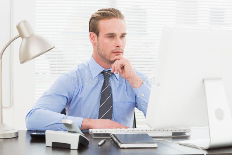 Hombre de negocios que piensa con la mano en la barbilla imagen de archivo