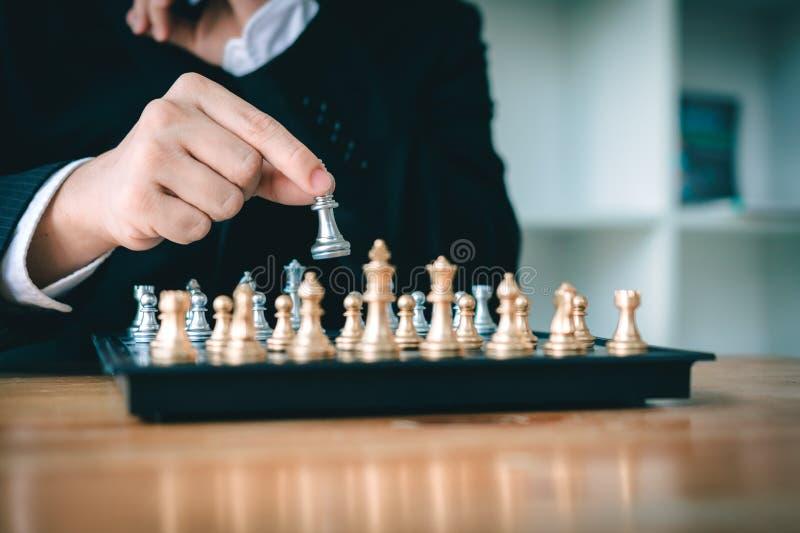 Hombre de negocios que piensa en el concepto y la mano de la estrategia que mueven al rey en un juego de ajedrez para el triunfo fotos de archivo libres de regalías