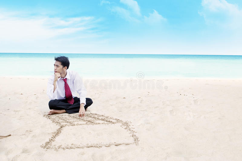 Hombre de negocios que piensa en una playa fotografía de archivo libre de regalías