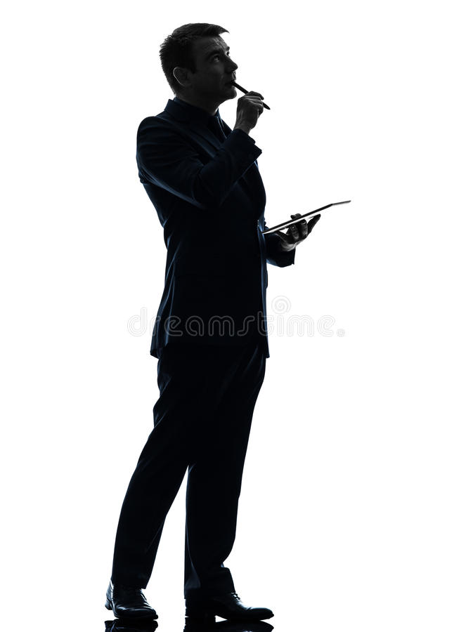 Hombre de negocios que piensa la silueta digital pensativa de la tableta imagenes de archivo