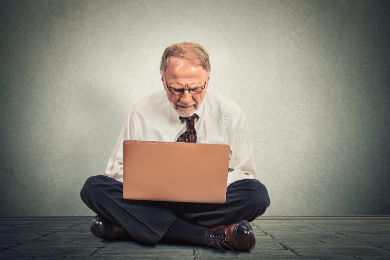 Hombre de negocios que piensa y que se sienta en el piso que trabaja en el ordenador imágenes de archivo libres de regalías
