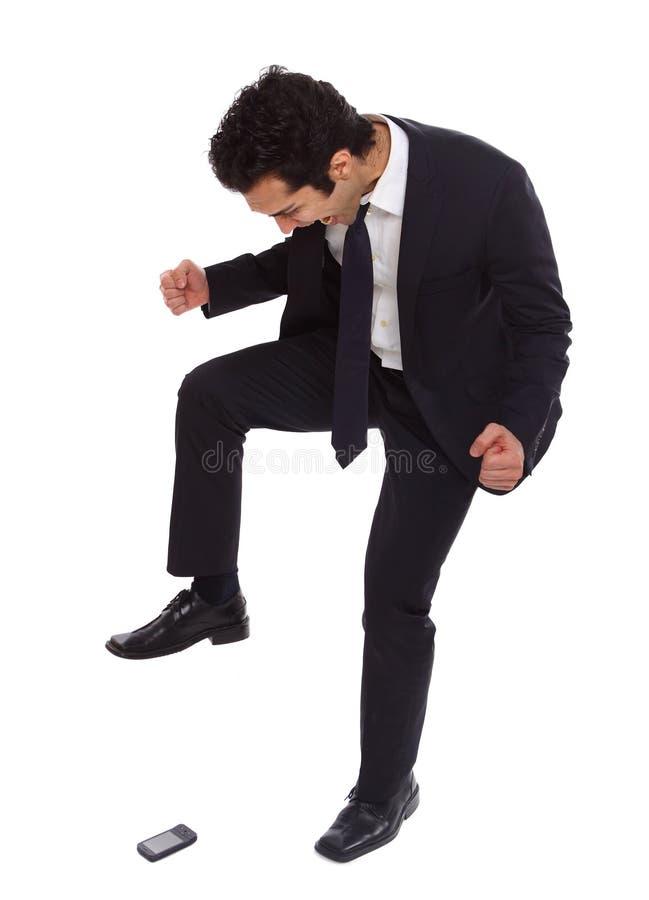 Hombre de negocios que pisa fuerte en su phoneq imagen de archivo