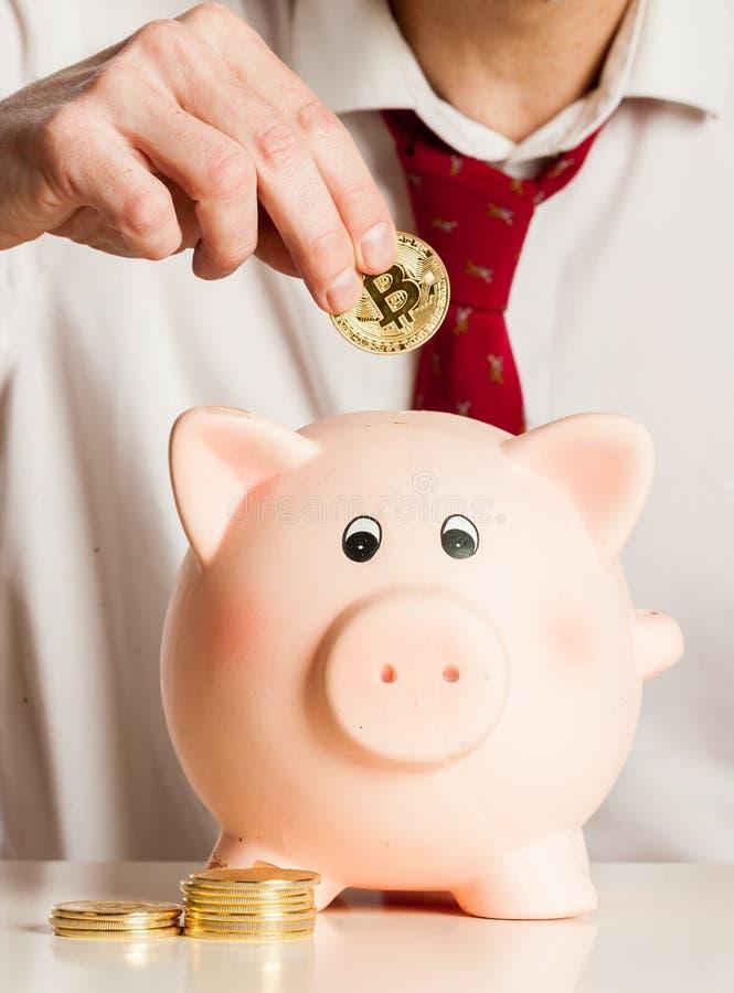 Hombre de negocios que pone bitcoins en una hucha foto de archivo libre de regalías