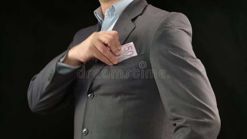 Hombre de negocios que pone el dinero en bolsillo, inicio acertado y renta rentable fotos de archivo libres de regalías