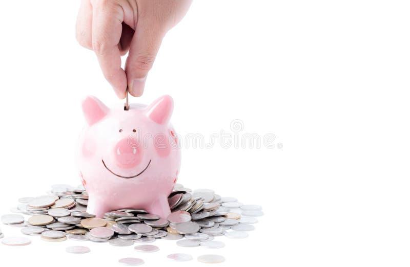 Hombre de negocios que pone la moneda en la hucha rosada aislada imagen de archivo