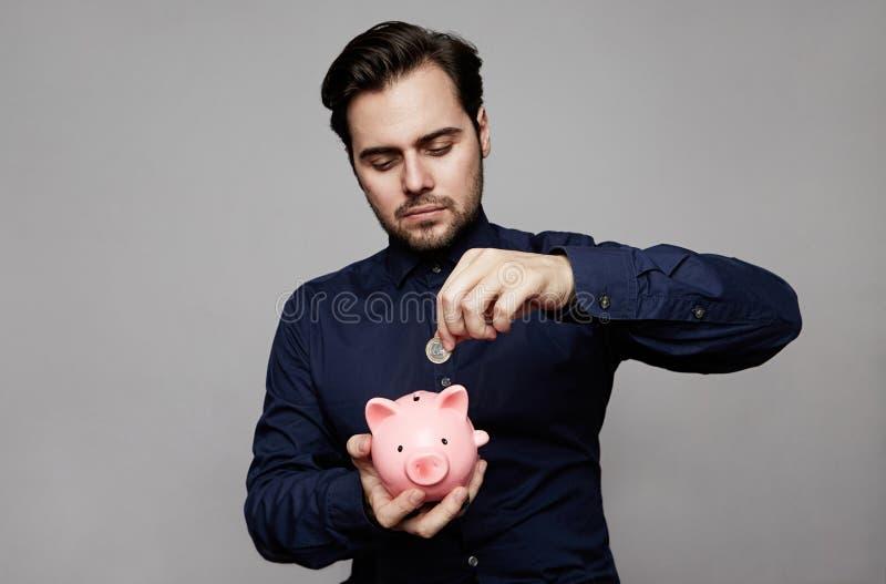 Hombre de negocios que pone la moneda en la pequeña hucha rosada fotos de archivo