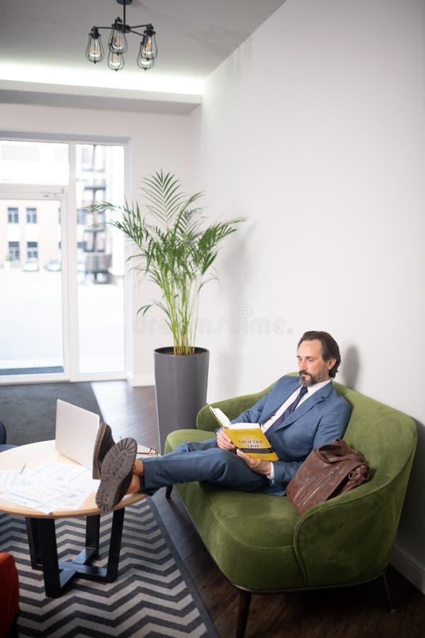 Hombre de negocios que pone las piernas en el libro de lectura de la tabla que tiene pequeña rotura imagen de archivo
