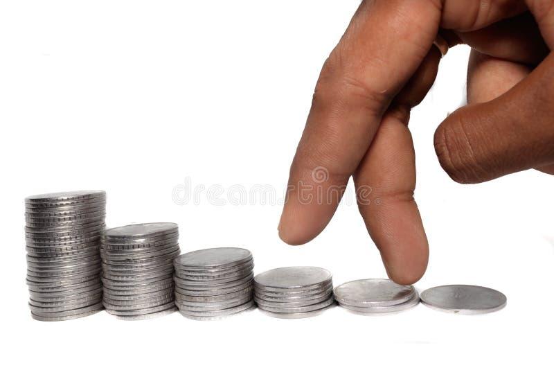 Hombre de negocios que pone los fingeres en moneda y que busca el aumento de beneficios para arriba, recogiendo el dinero con el  imagen de archivo