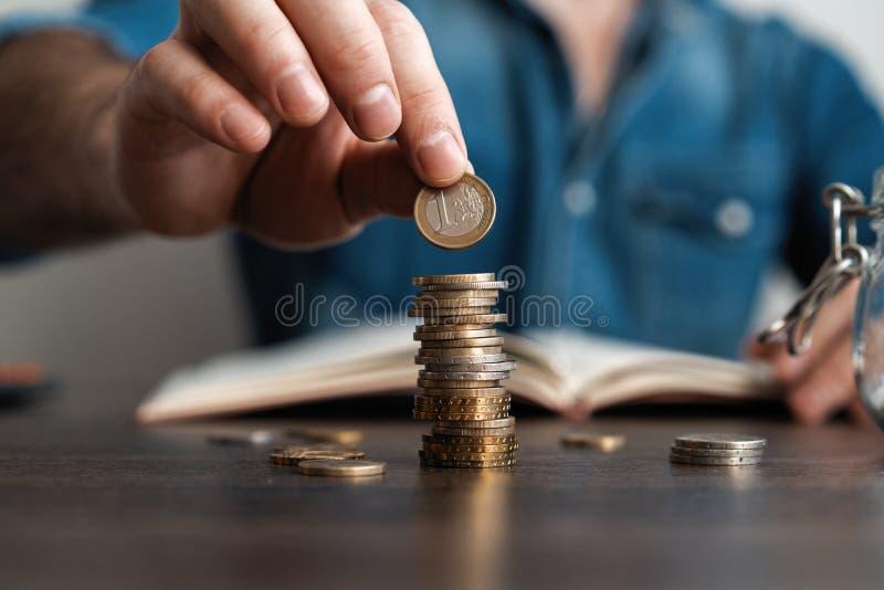 Hombre de negocios que pone una moneda en la caja de ahorros de la pila de las monedas y explicar su dinero todo en concepto de c imagen de archivo