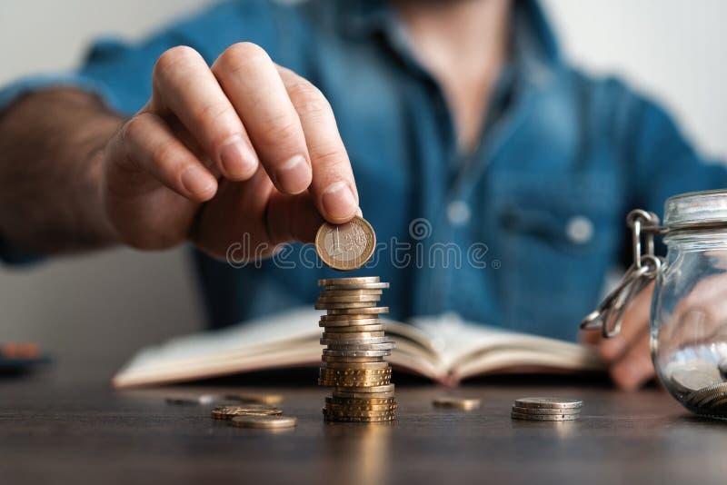 Hombre de negocios que pone una moneda en la caja de ahorros de la pila de las monedas y explicar su dinero todo en concepto de c foto de archivo