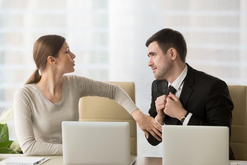 Hombre de negocios que pregunta a colega femenino acerca de favor imagenes de archivo