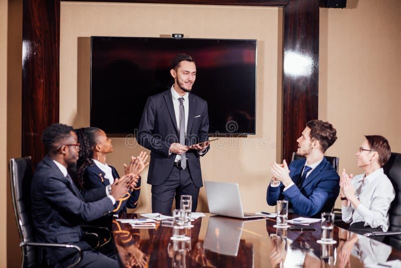 Hombre de negocios que presenta a los colegas en la reunión imagen de archivo
