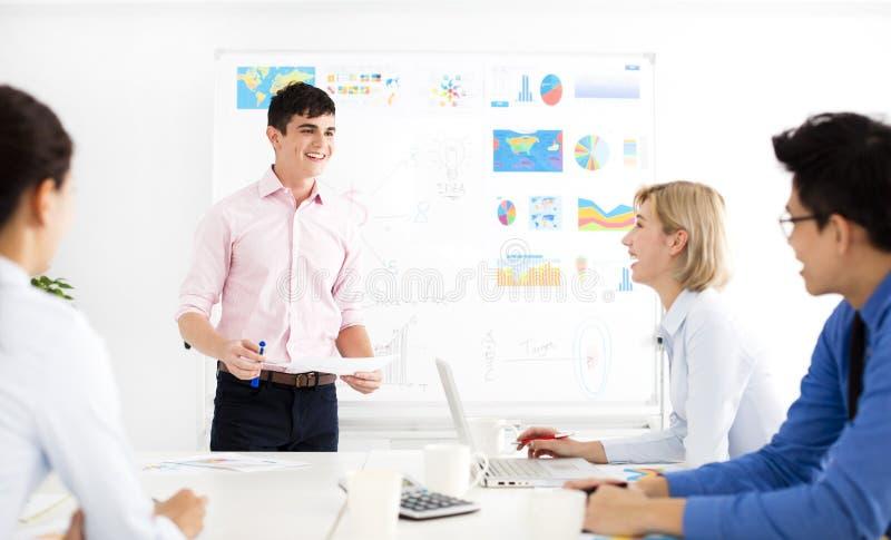 Hombre de negocios que presenta a los colegas en la reunión imágenes de archivo libres de regalías