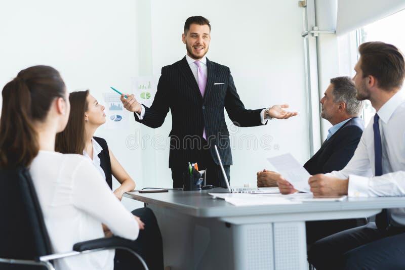 Hombre de negocios que presenta a los colegas en una reunión imágenes de archivo libres de regalías