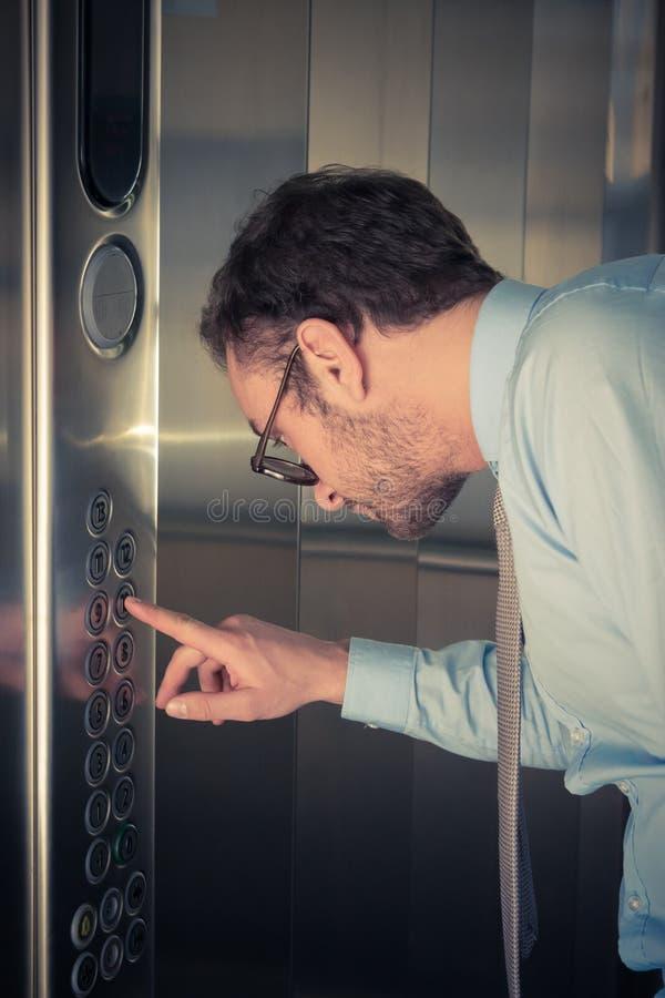 Hombre de negocios que presiona el botón en el elevador fotos de archivo