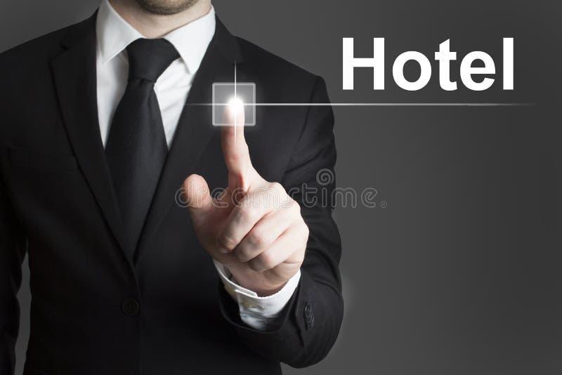 Hombre de negocios que presiona el hotel virtual del botón foto de archivo
