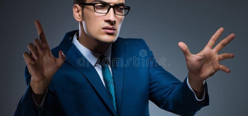 Hombre de negocios que presiona los botones virtuales en fondo gris imagen de archivo libre de regalías