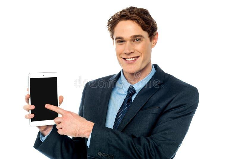 Hombre de negocios que promueve la tableta nuevamente lanzada imágenes de archivo libres de regalías