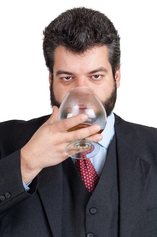 Hombre de negocios que prueba un vidrio de whisky imágenes de archivo libres de regalías