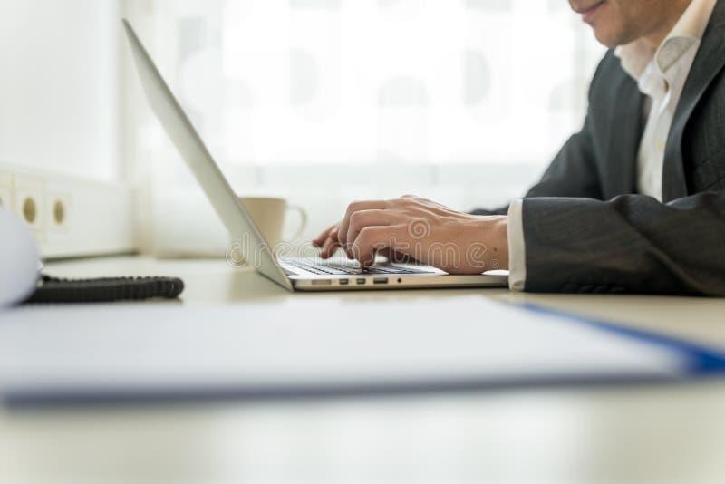 Hombre de negocios que pulsa en el ordenador portátil imagen de archivo