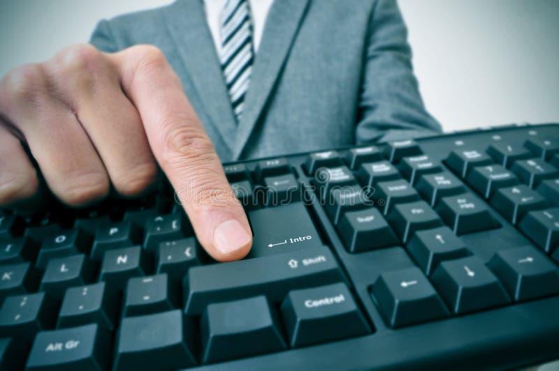 Hombre de negocios que pulsa la tecla de la introducción de un teclado de ordenador imagenes de archivo