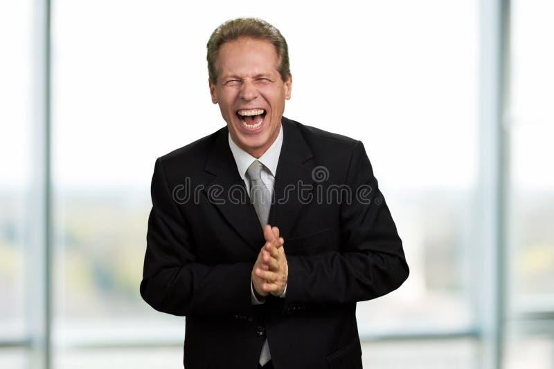 Hombre de negocios que ríe con los ojos cerrados fotos de archivo