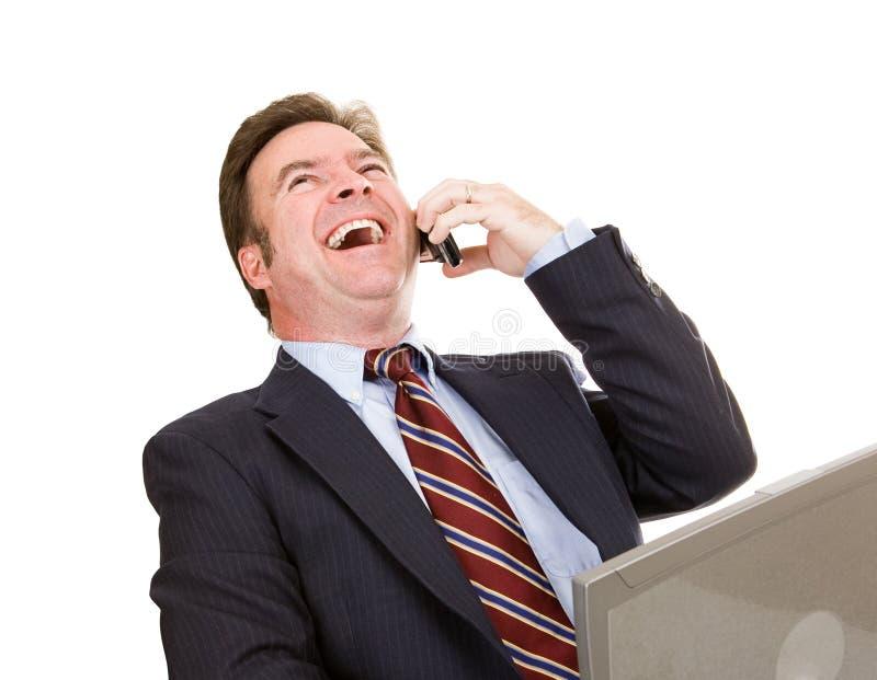 Hombre de negocios que ríe en el teléfono imagenes de archivo