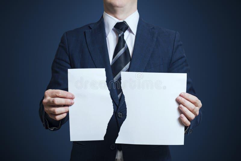 Hombre de negocios que rasga el papel en blanco aparte fotografía de archivo libre de regalías