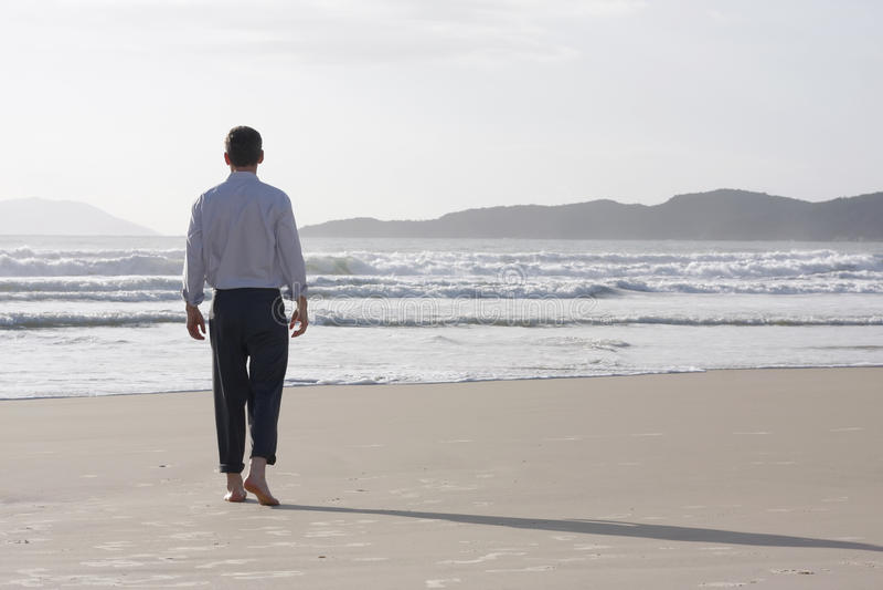Hombre de negocios que recorre descalzo en una playa fotografía de archivo