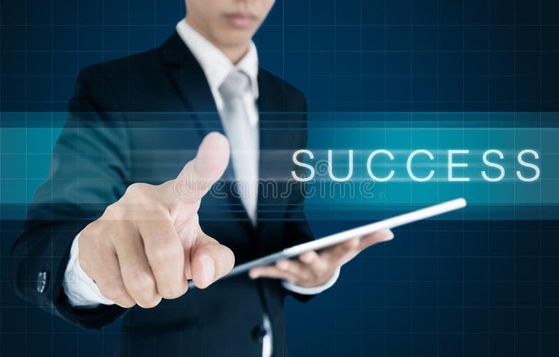 Hombre de negocios que resbala en la pantalla con palabra del ÉXITO Concepto del éxito de asunto foto de archivo
