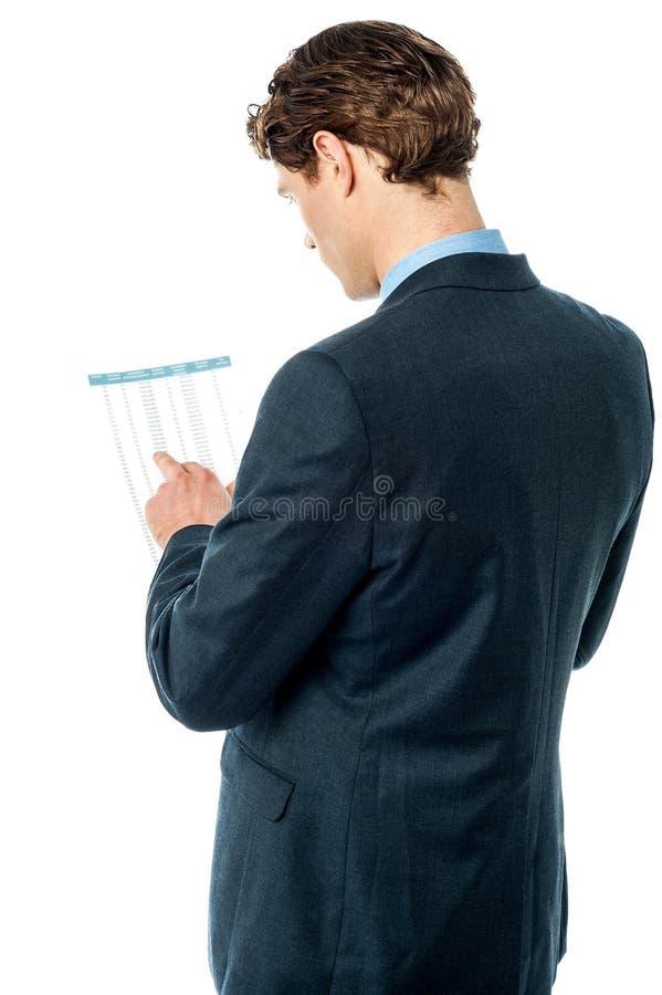 Hombre de negocios que revisa el informe de negocios imagen de archivo libre de regalías