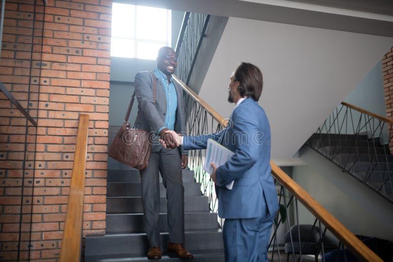 Hombre de negocios que sacude la mano del colega mientras que reunión sobre escalera imagen de archivo libre de regalías