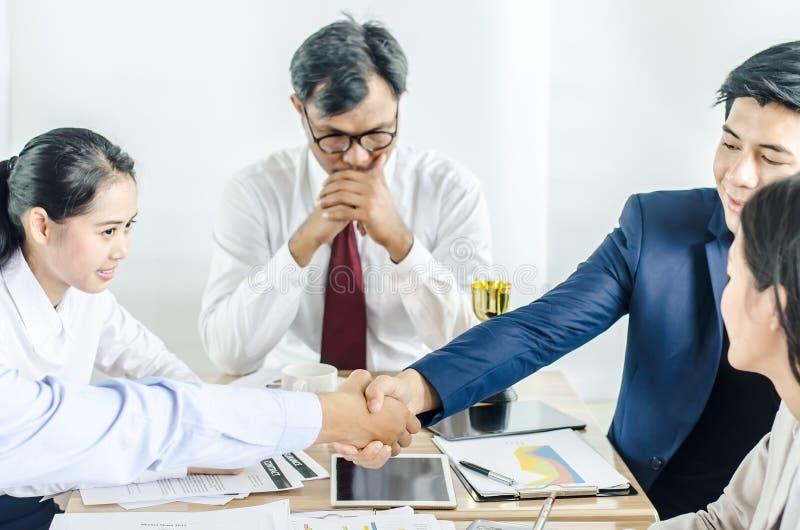 Hombre de negocios que sacude las manos para sellar un trato con su socio y colegas después de acabar para arriba que se encuentr foto de archivo libre de regalías