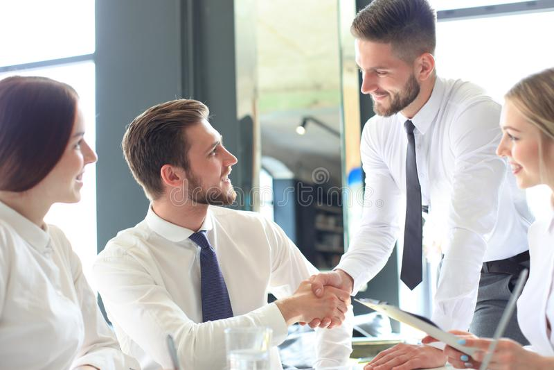 Hombre de negocios que sacude las manos para sellar un trato con su socio y colegas en oficina imagenes de archivo