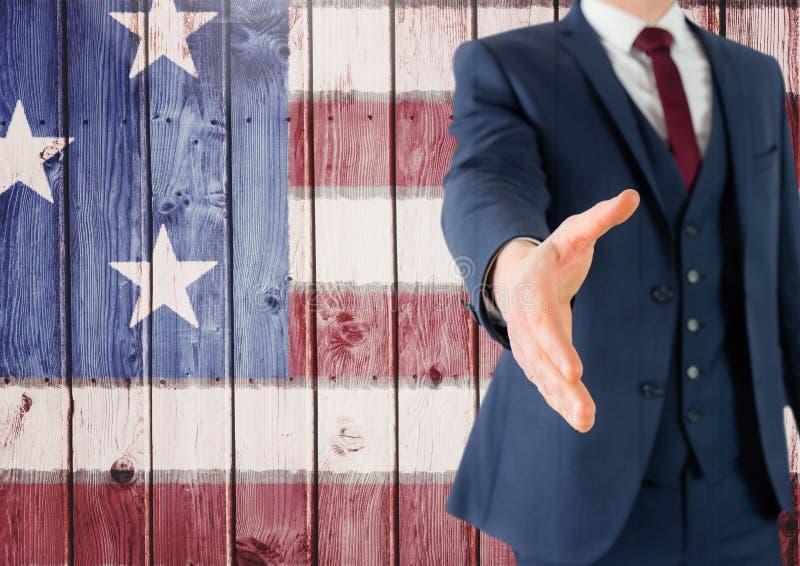 Hombre de negocios que sacude su mano contra bandera americana imágenes de archivo libres de regalías