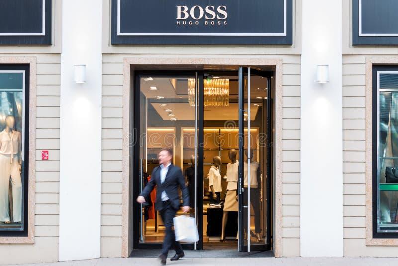 Hombre de negocios que sale de la tienda de la moda de Hugo Boss foto de archivo